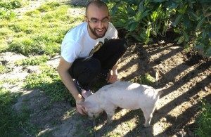 DxE investigator Samer Masterson hanging out with one of the pigs rescued from the Farmer John farm. Photo by Michael Goldberg.